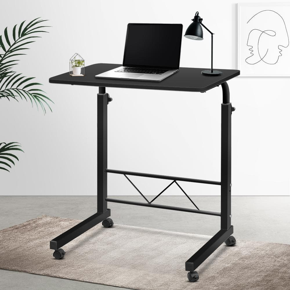 Artiss Mobile Laptop Desk Laptop Table Sometimes you wish you have a ready desk at your beck and call. But moving your one desk is impractical. And that is where our Mobile Laptop Desk can help you explicitly.Designed to be strong and lightweight, our Mobile Laptop Desk has ample desk area to work efficiently without feeling cluttered. The height is easily adjustable to your preference and the U-shape design fits in well with most furniture such as sofas and beds to get a comfortable sitting position. The castor wheels rotate 360? and can be readily locked down in place. Or, if you like, remove the detachable wheels for a more permanent fixture. Not least, with its thick 17mm MDF board desk top and sturdy powder-coated H-shape steel frame, our Mobile Laptop Desk is absolutely versatile to function as any type of table top.Say goodbye to being tied down to one desk location. Welcome to our Mobile Laptop Desk. Get yours today.FeaturesPortable and lightweight360? rotating laptop standLarge and smooth surfaceClassic matte finishHigh flexibility and mobilityH-shape steel frameU-shape designRound edgesDouble knobs for height adjustmentAdjustable stand heightWall-leaning designDetachable and lockable caster wheelsSpecificationsTabletop: MDF boardThickness: 17mmMaximum weight capacity: 40kgHeight adjustment: 65 – 97cmOverall dimension: 60 × 40 × 65 – 97cmColour: BlackPackage ContentMobile Laptop Desk x 1Assembly Manualx 1